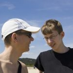 man in baseball cap with teenage boy in glasses
