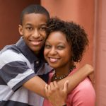Black teenage boy hugging Black woman, both smiling.