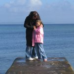 mother and daughter hug on shoreline