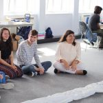 photo of young people sitting on floor, smiling
