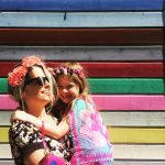 Photo of mum and daughter with flower garlands in front of brightly striped planks