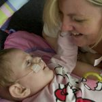 baby with nasal tube touching the face of a smiling woman