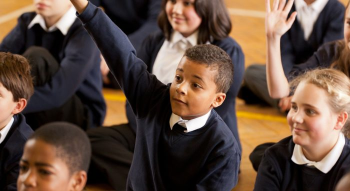 boy holding up hand in assembly