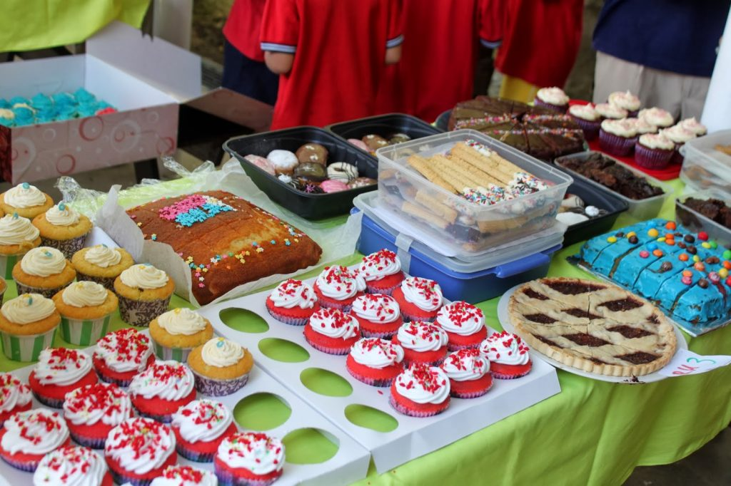 table filled with colourful cakes at school event