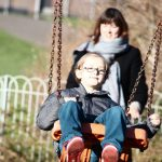 mum pushing son on swing