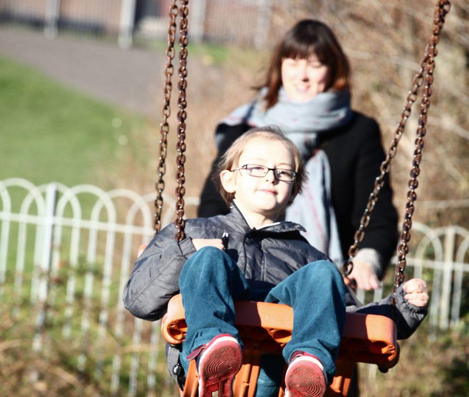 mum pushing son on swing
