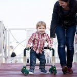 disabled toddler and mum walking towards camera