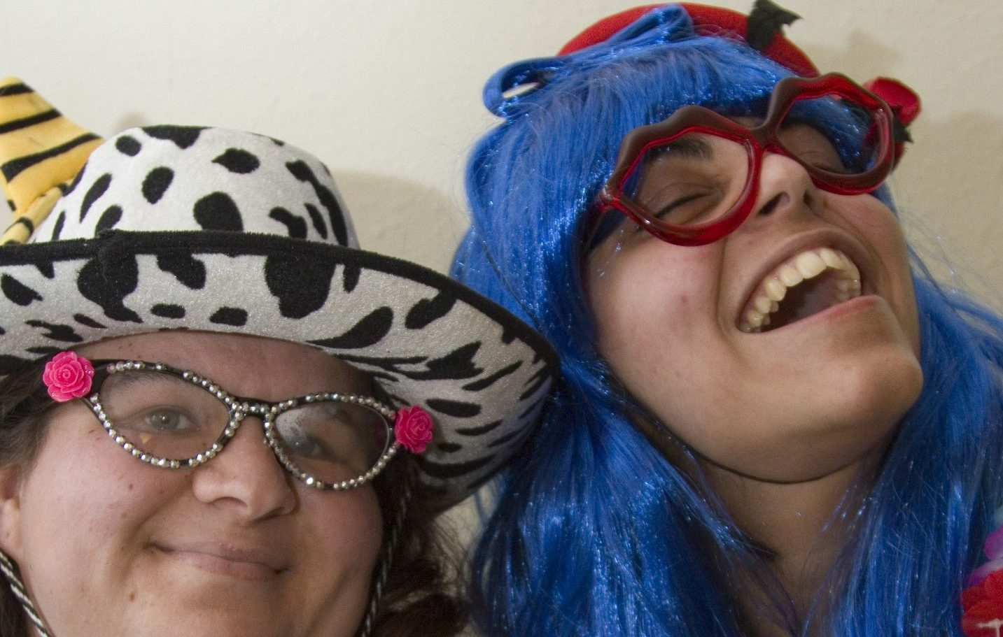 two young women wearing wigs, hats and silly glasses