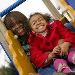 grinning mum and child on slide