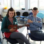 young woman playing small guitar, sat next to a young man