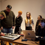 Young people using a laptop and a panel with lots of dials