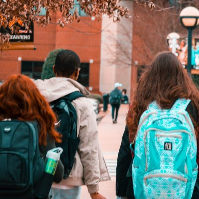young people wearing backpacks facing away from the camera and heading toward a large brick building