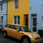 yellow Ford Mini car in front of a yellow house