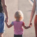 parents holding child's hands