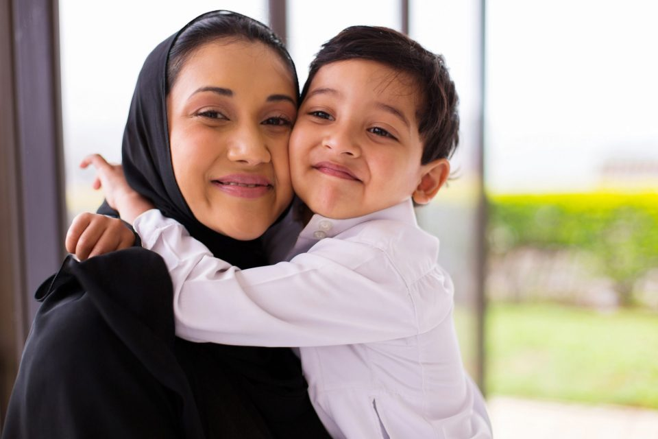 smiling woman in a hijab being hugged by her young son