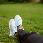 feet in trainers of someone sitting on grass