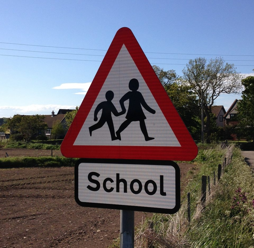 "traffic sign saying ""school"" with image of children"