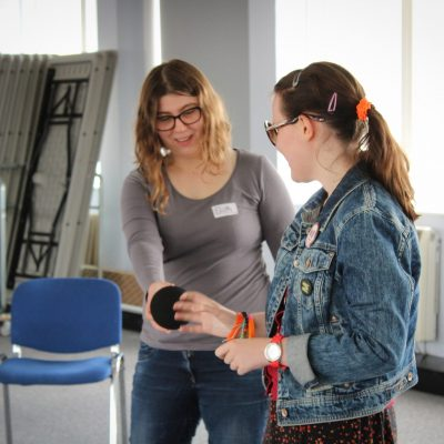"a young woman with lightly curly hair, glasses and a name tag reading ""Eliph"" handing a ball to another young woman in dark glasses and a denim jacket, both smiling."
