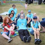 group of young people sat on the grass, some wearing blue Amazing Futures t-shirts, some with face-paint on