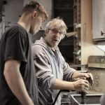 Young man watches an older man using tools in a workshop
