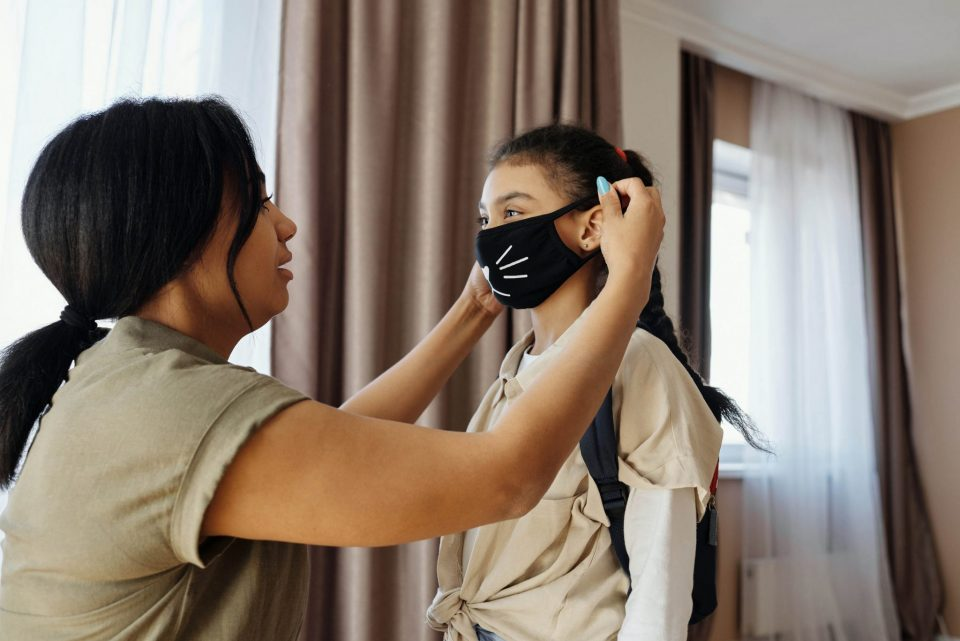 woman helping a young girl put on a face mask with a motif of cat's whiskers on it