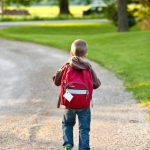 young boy with a backpack on walking away from the camera