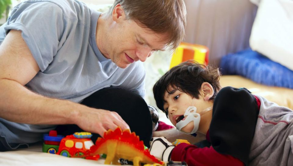 boy with prosthesis on jaw playing with dinosaur toys with middle-aged man
