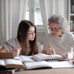Teenager girl studying with older woman with grey hair