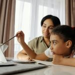 Brown woman and pre-teen girl sit together at a table, the girl gesturing with a pen