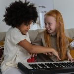 two girls playing a keyboard together, one smiling broadly
