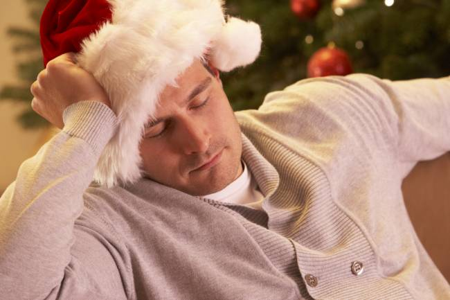 Man with his eyes closed wearing a santa hat