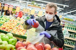 Man in supermarket wearing a mask and putting an apple in a bag