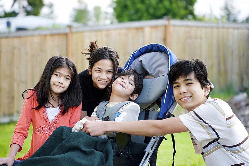 Disabled Asian boy in motorised wheelchair with smiling family