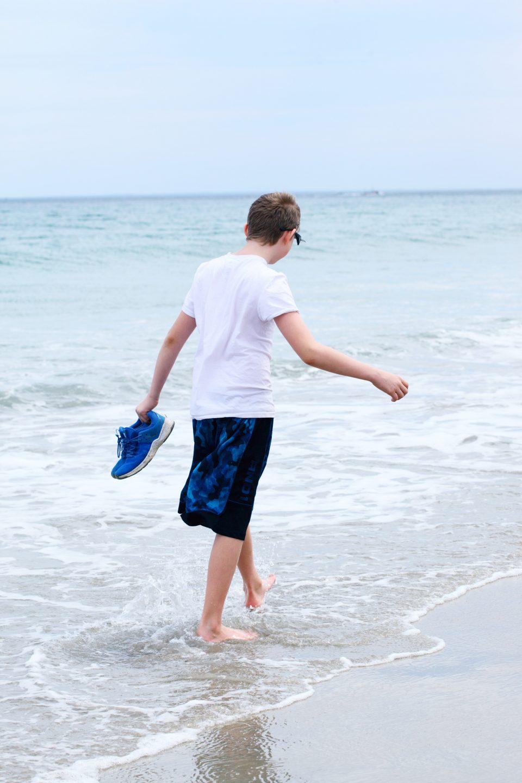 older boy strolling on shore
